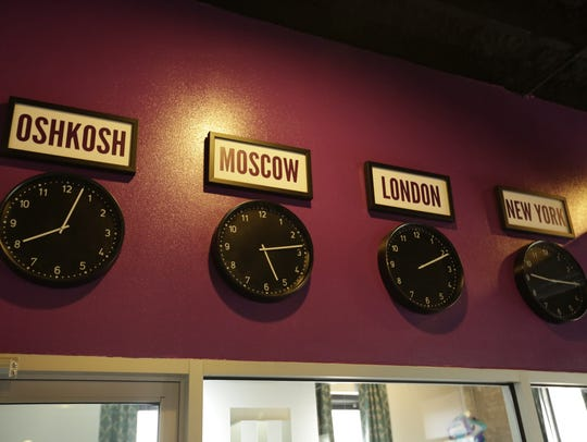 Clocks on a wall at Candeo Creative show the time of