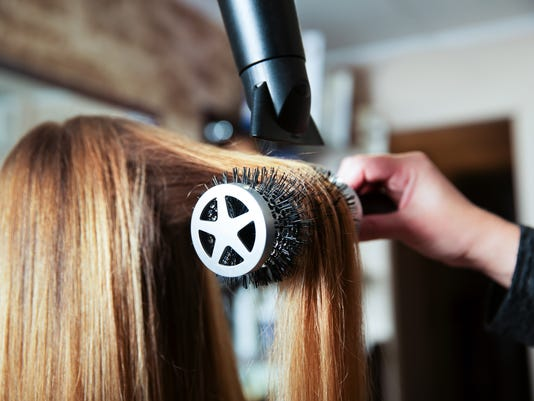 Making hairstyle using hair dryer.