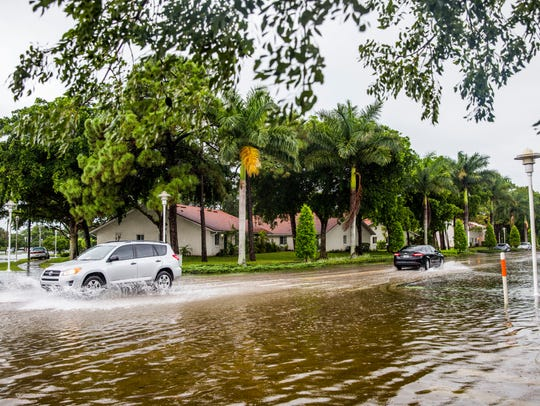 Cars drive through a flooded 5th Avenue North in River