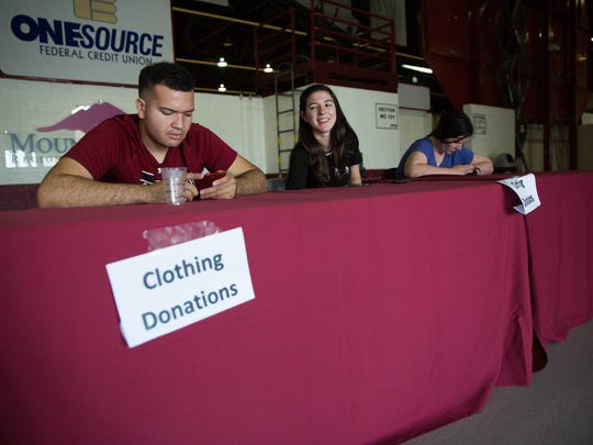 Kai Williams, Kathleen McClellan and Tyra Font sitting at one of the clothing donation stands set up at the Pan American Center Tuesday Aug. 29, 2017 for victims of Hurricane Harvey in Texas. The clothing drive was held Tuesday and Wednesday.
