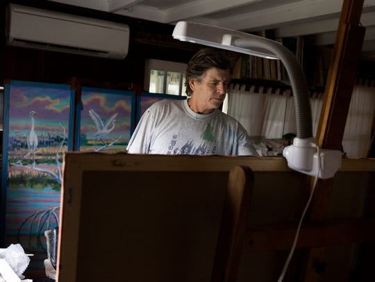 Artist Paul Arsenault paints in his home studio Monday,