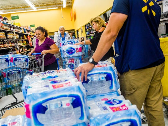 People line up for cases of water at Walmart on Immokalee Road on Wednesday, Sept. 6, 2017, in preparation for Hurricane Irma.