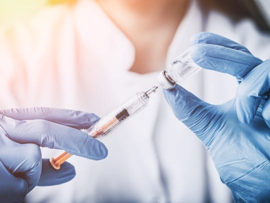 A woman injects a vaccine vial.