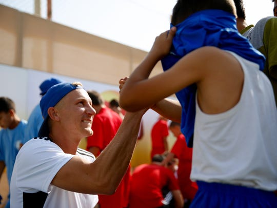 Former pro soccer player Steven Lenhart helps a Syrian refugee child pull on a donated jersey before a Kickstart Joy soccer clinic at the Zaatari camp.