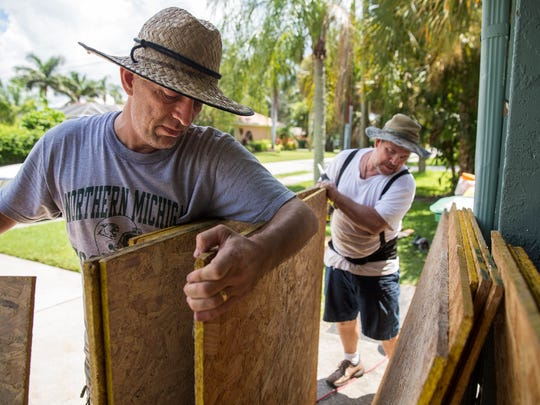 Doug Lopez, left, and Doug McMillan boarded up the windows of a client's home in Naples Park on Thursday, Sept. 7, 2017 in preparation of Hurricane Irma's arrival.