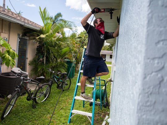 Tyler Bess helps out, drilling anchor points into his father's home before boarding up the windows in Naples Park on Thursday, Sept. 7, 2017 in preparation of Hurricane Irma's arrival.