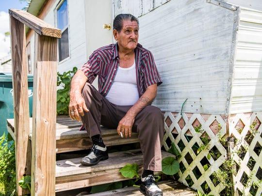 Eusebio Rosas smokes a cigarette on the steps of his