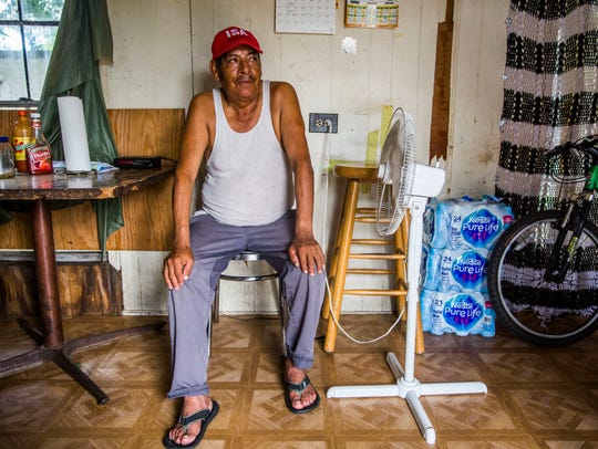 Uriel Cruz, 70, sits in front of his fan in his trailer