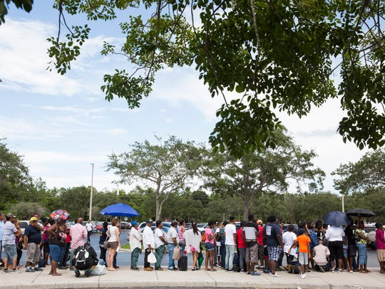 Residents wait patiently outside Lely High School,