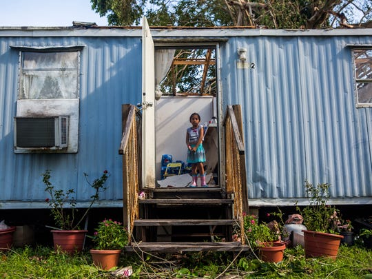 Maria Romero, 6, stands in the doorway of her home the morning after Hurricane Irma came through Immokalee on Monday, Sept. 11, 2017. The storm ripped off the roof of her family's trailer. The family has nowhere to go.