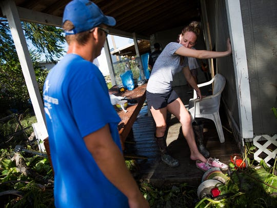 Tatum Johnson takes a moment to breathe while putting on her boots as she helps to clear out Michael Kelley's damaged home on Chokoloskee on Monday, September 11, 2017 after Hurricane Irma.