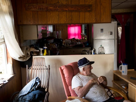 Dwain Daniels, 81, sits inside his home after a long