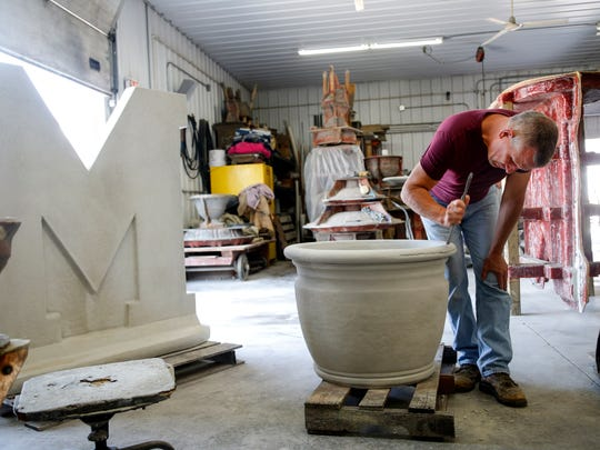 Dennis Meyer, owner of Created In Johnston works on a planter in his shop Tuesday, Sept. 12, 2017.