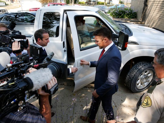 Chris Soules is escorted by his lawyer Brandon Brown to his father's truck after a hearing in Buchanan County District Court Thursday, Sept. 14, 2017, in Independence, Iowa. Reality TV star Soules is charged with leaving the scene in a fatal April crash near Aurora, Iowa.