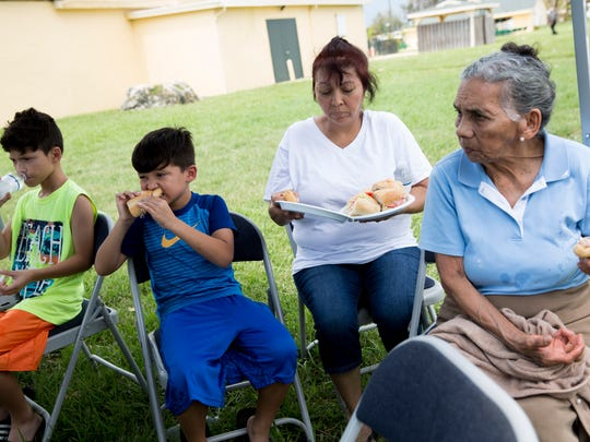 Jamio Bonilla, 9, from left, his brother Johan, 6, their aunt Mirtha Baca and grandmother Sergia Hernandez, all of Golden Gate Estates, grab a quick bite to eat while  applying for federal assistance through FEMA at Naples Estates, a mobile home community off of Rattlesnake Hammock Road, Thursday, September 14, 2017 in Naples, Fla.