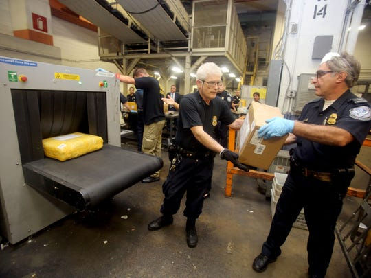 U.S. Customs and Border Protection officers put packages through an X-ray machine at the JFK mail inspection site.
