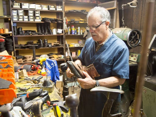 Rogelio Cabrera, puts a new sole on a boot at his store,