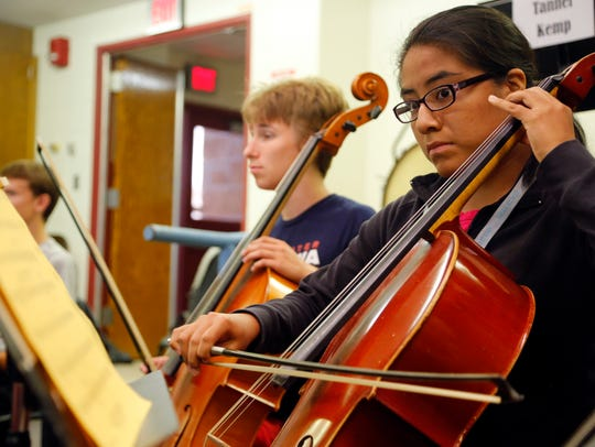Wendy Flores plays the cello during an orchestra practice