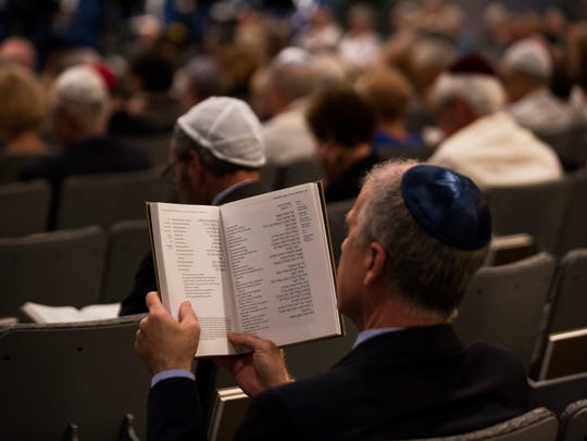 A man reads from the prayer book Mishkan Hanefesh during