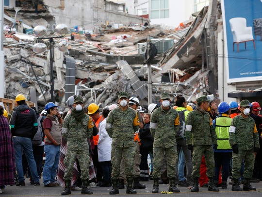 Soldiers stand next to a collapsed building where rescue
