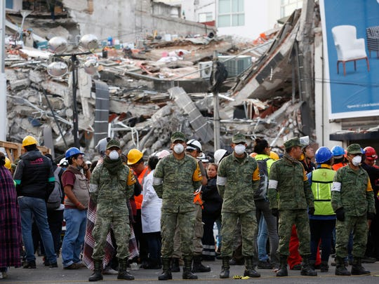 Soldiers stand next to a collapsed building where rescue workers race against the clock to reach possible survivors trapped inside a office building in the Roma Norte neighborhood of Mexico City, in the early morning hours of Saturday, Sept. 23, 2017. A 7.1 magnitude earthquake Tuesday toppled more than three dozen buildings in the capital, leaving at least 46 people believed missing in this office building alone.