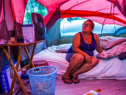 Samantha Tindell sits on a mattress in a tent outside