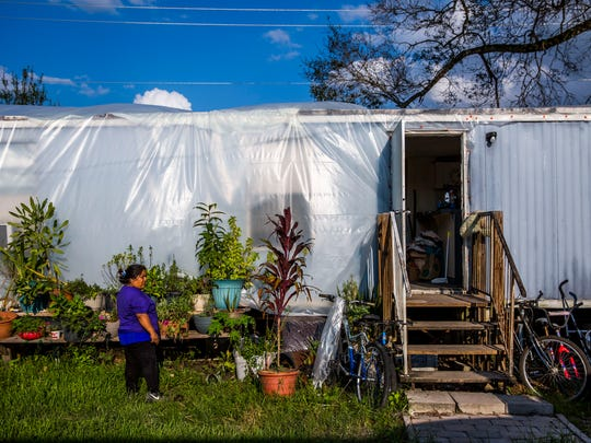 Maura Diaz walks outside of her damaged Immokalee trailer on Thursday, Sept. 21, 2017. Plastic is wrapped around the trailer to prevent water from seeping in through holes in the roof.