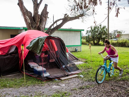 Makayla Tindell, 11, rides her bike by the tent outside her family's damaged Immokalee trailer Friday, Sept. 22, 2017. Makayla and her brother and parents had been sleeping in the tent due to damage and mold in their home, until a thunderstorm flooded their tent after this photo was taken.