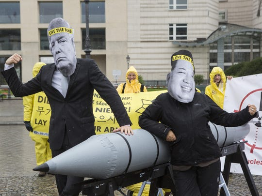 Activists wearing masks to look like President Donald Trump and North Korean leader Kim Jong-Un pose next to a Styrofoam effigy of a nuclear bomb in front of the American embassy on Sept.13, 2017 in Berlin, Germany.