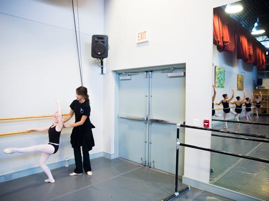 Curran Tellalian makes small adjustments to Amelia Painter's form during a technique class on Monday, September 25, 2017 at the Naples Academy of Ballet in Naples.