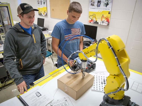 Ivy Tech students Trevor Snavely, left, and Benjamin Wolfe work on coding a robotic arm to move through a set range of motions needed in automation. Ivy Tech caters not only to recent high school graduates and people who want job retraining to recapture past jobs but also people who are working but want to improve their job skills for other jobs.