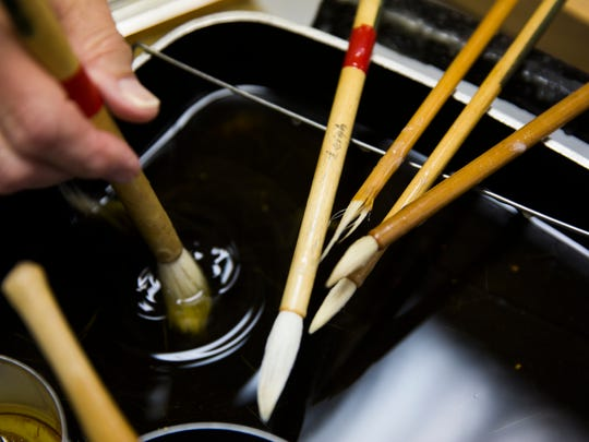 Leigh Herndon dips her brush into a pan of hot wax on Thursday, August 31, 2017 at her studio in the art district in North Naples. Herndon uses a Japanese art form called Rozome which is a wax-resist fabric dyeing technique.