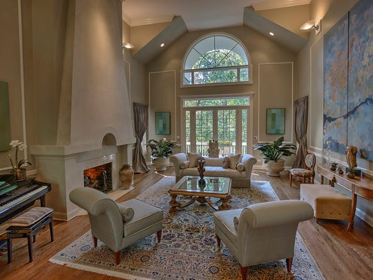 The two-story living room has a dramatic fireplace, picture-frame trim, a chair rail and tall French doors to the deck, crowned by a circle-top windows.