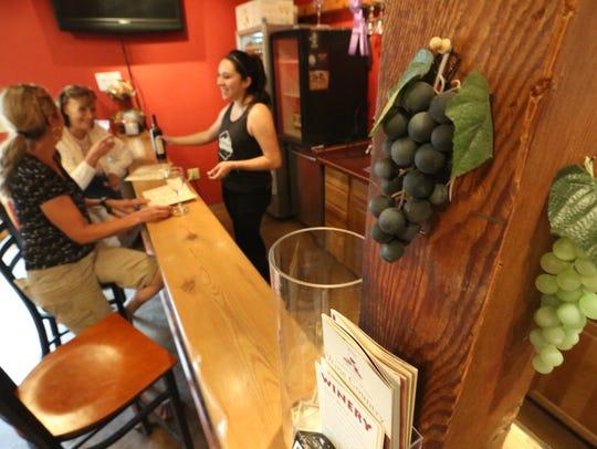 Gigi Smith, foreground, and Audrey Ziegler taste wine