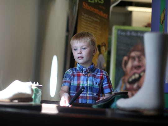 Charles Davis, 4, plays cobbler at the Children's Discovery
