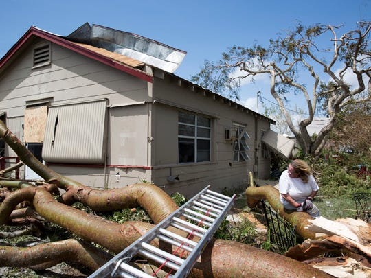 Margie Hackett looks back at her home, which was nearly hit the day before by a falling tree during Hurricane Irma, in Goodland, Fla., on Monday, Sept. 11, 2017.