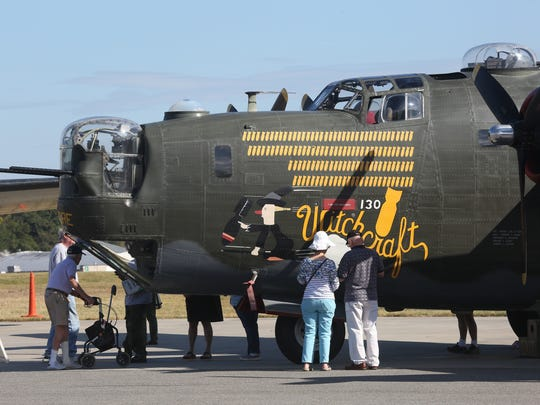 Visitors look over one of the WWII bombers  on display