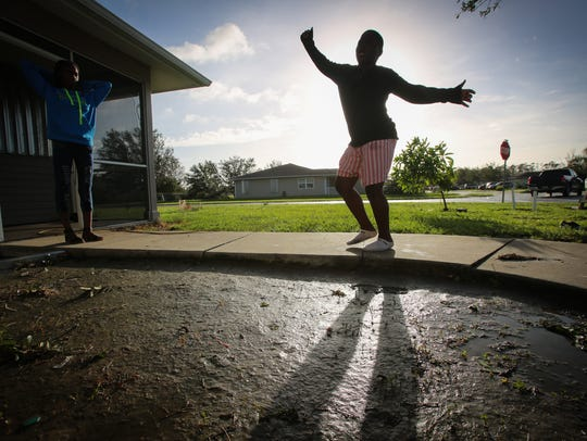Izzy Lobe, 11, dances in front of his flooded yard