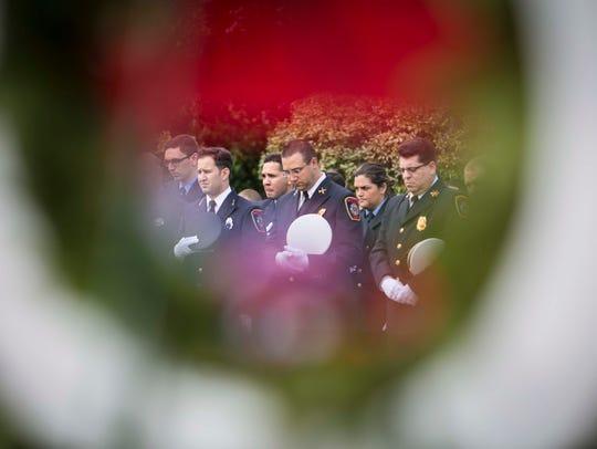 Seen through a wreath, firefighters bow their heads