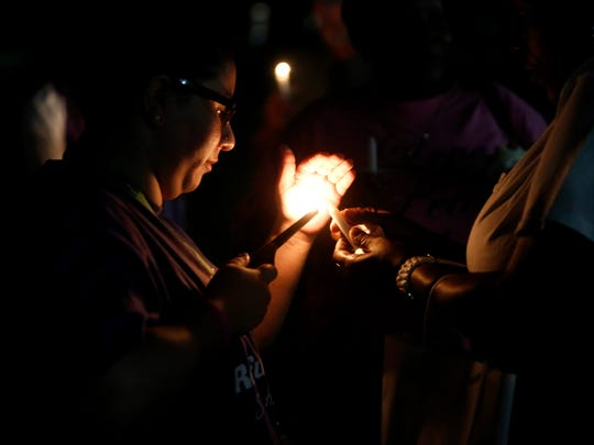 Attendees light candles in memory of those who lost