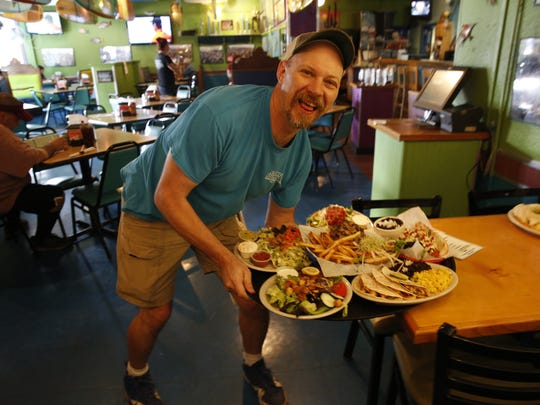 Scott Roberts says he's been working at Cabos Island Bar and Grill on and off for 17 years. He serves lunch at the Apalachee Parkway restaurant Oct 17.