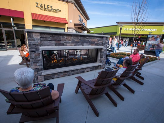 Shoppers take a break at the outdoor fireplace during the opening the Outlets of Des Moines in Altoona in October 2017. The 300,000-square-foot shopping center has more than 40 stores, with more expected to be announced this year.