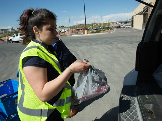 April Quezada, a personal shopper in the Online Grocery Pickup department at the Walmart on Rinconada Boulevard, places a customer's groceries into their vehicle. Thursday October 19, 2017.