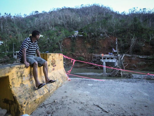 A man sits on the edge of a broken bridge spanning
