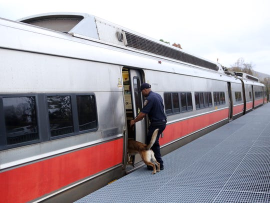A canine leads an officer inside a rail car to find