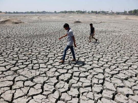 Indian boys walk through a dried patch of Chandola