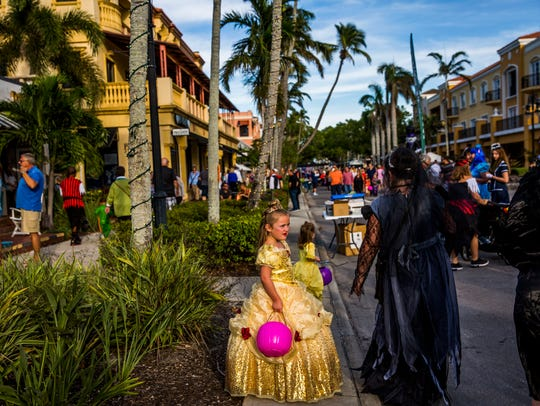 People walk down 5th Avenue South during Spooktacular