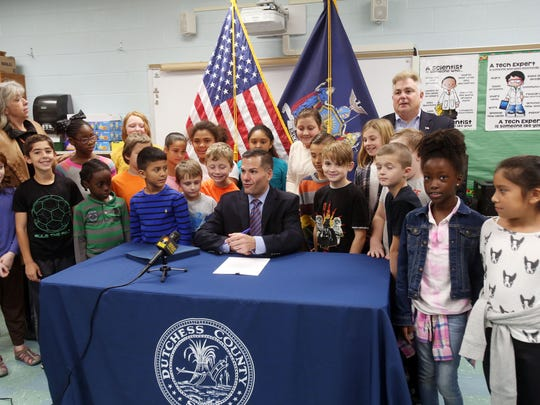 Dutchess County Executive Marc Molinaro is surrounded by Joseph D'Aquanni West Road Intermediate School third graders as he signs a law banning the use of polystyrene foam food containers in the County by chain food service establishments Nov. 3, 2017. Third-grade students there apparently inspired the law.