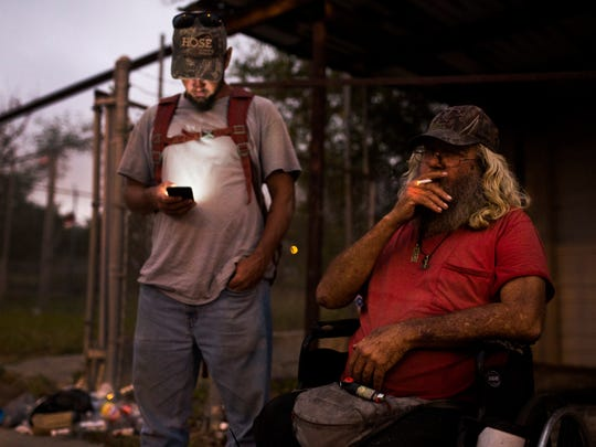 Marc Monroe, 63 (right), and his son, Clint Monroe, meet up and talk before they return to their shelters for the night on Tuesday, Oct. 31, 2017.