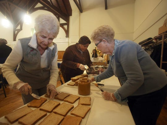 """Volunteers Marie Shepitka, Mavis, Nyakoa, and Joan Dosch-Freire, all of Nyack, make peanut butter and jelly sandwiches to given to the needy after they are served a sit-down dinner the Soup Angel's soup kitchen at the First Reformed Church in Nyack Nov. 11, 2017. The sandwiches are part of a """"bounty bag"""" given to dinner guests as they leave the soup kitchen."""